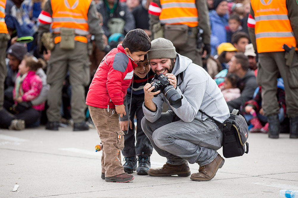 Flüchtlinge warten vor dem Sammelzentrum an der Slowenisch-Österreichischen Grenze im Gebiet von Spielfeld am Donnerstag, 22. Oktober 2015. Im Bild zeigt ein Fotograf Flüchtlingskindern seine Bilder.